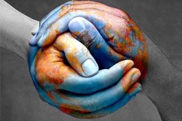 Két festett kéz fogja egymást egy földgömböt ábrázolva