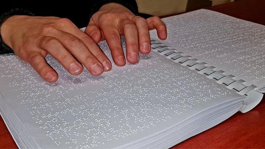 egy férfi éppen egy braille könyvet olvas az ujjai segítségével