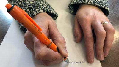 egy női kéz egy narancssárga színű tollal, éppen az aláírását gyakorolja