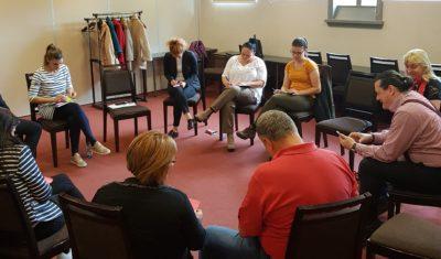 A résztvevők körben ülnek és beszélgetnek, jegyzetelnek