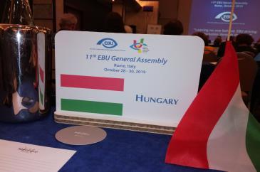 A magyar delegáció asztal táblája, mellette zászló, a háttérben EBU logó