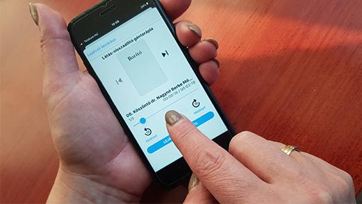 hangos könyvtár applikációt használja egy női kéz